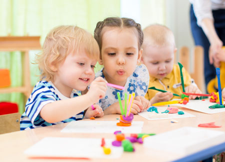 three students playing in class in the children's learning center in Woodstock