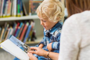 Schoolboy with teacher looking at picture book in library