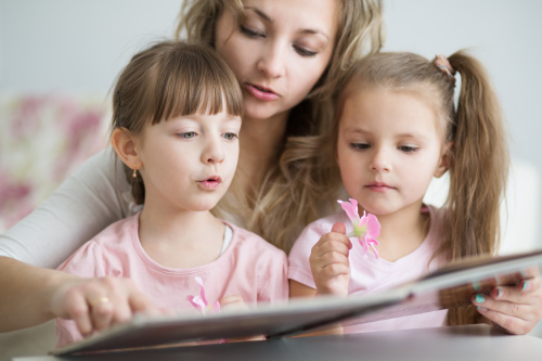 happy mother with sweet little daughters reading book