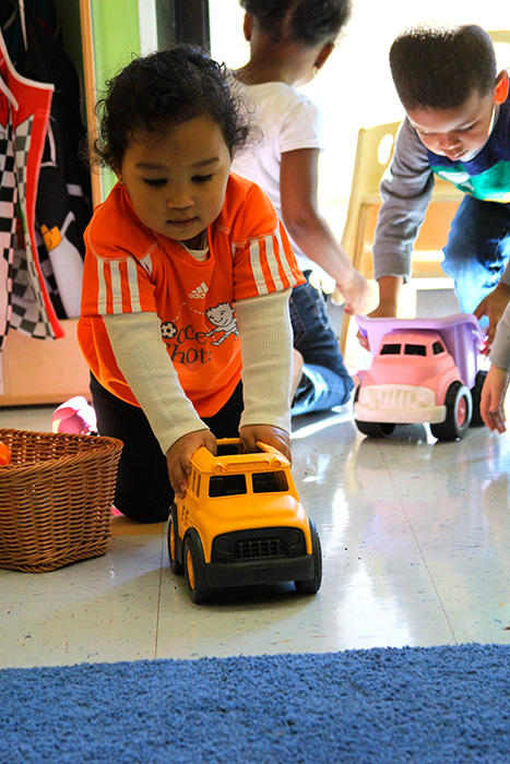 a girl playing with a toy car