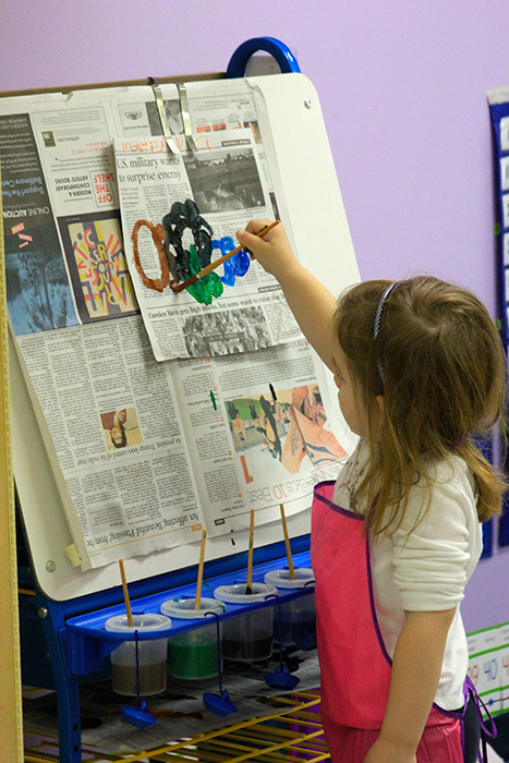 A kid painting on a newspaper