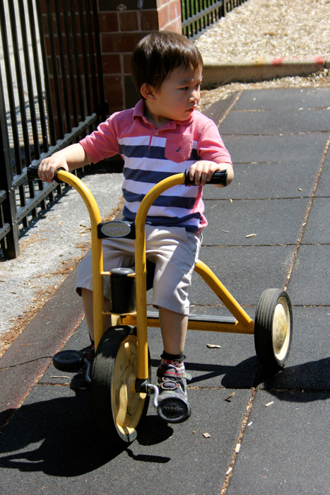 a boy riding a tricycle
