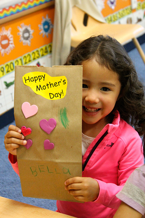 A girl holding Happy Mother's Day card