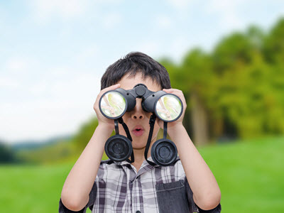 boy at summer camp in Woodstock looking through binoculars