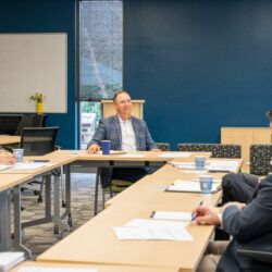 CEO, Richard Huffman, sitting in meeting space with advisors