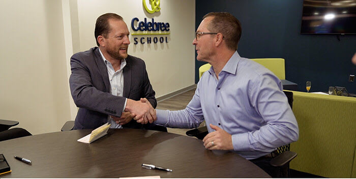 shaking hands after signing documents for owning a franchise